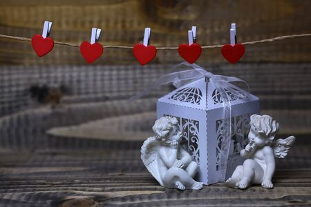 putto: Closeup view of two beautiful cupid angels decorative figurine near white paper greeting valentine box near red clothes-peg in shape of heart with no people on wooden background, horizontal picture