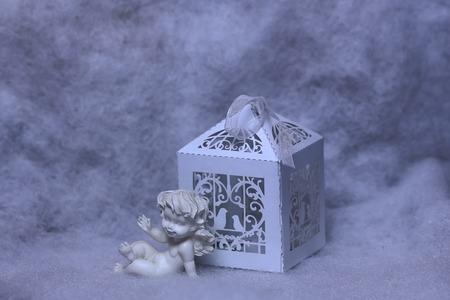wadding: Closeup view of one beautiful cupid angel decorative figurine near paper greeting valentine box on white wadding decorating snow background, horizontal picture Stock Photo