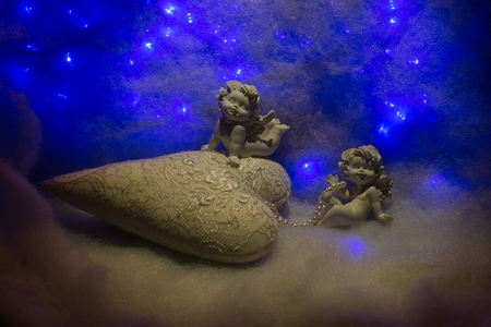 wadding: Closeup of beautiful soulful figurine composition of cupid angels for valentine day or christmas with small pillow in shape of heart lying on white wadding decorating snow with bright light sparks