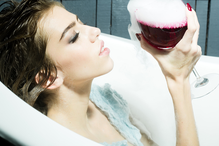 elixir: Primer de la mujer bastante joven sensual con el pelo mojado que se sienta en la pestaña de baño blanco que sostiene en la mano vaso con el líquido rojo con humo como elixir de belleza interior, cuadro horizontal