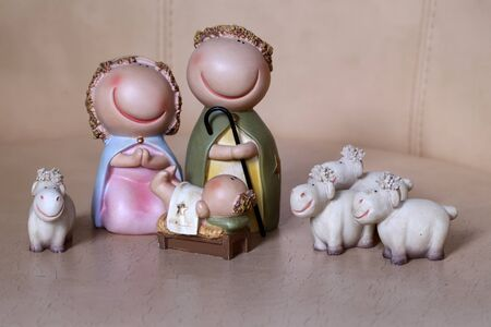 mother of jesus: Closeup view of decorative celbrating Christmas and Jesus birth figurines of holy vergin Mary Josepd newborn child with few white sheeps standing on light leather background, horizontal picture Stock Photo