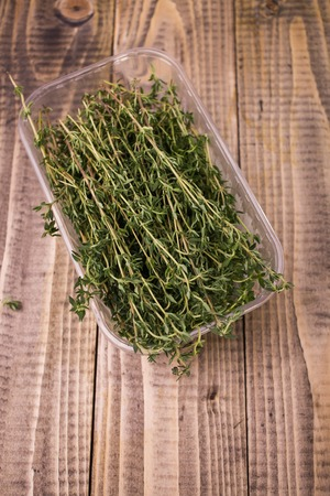 many branches: Many branches of aromatic fresh green colored herb rosemary ingredient for piquant taste of dish in plastic food container on wooden background top view closeup, horizontal picture Stock Photo