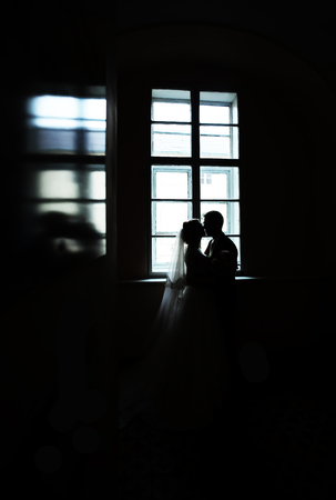 window opening: Photo full length of dark silhouette of bridal couple bride and groom kissing in window opening blazed into glossy surface on wedding day black and white on indoor background, vertical picture