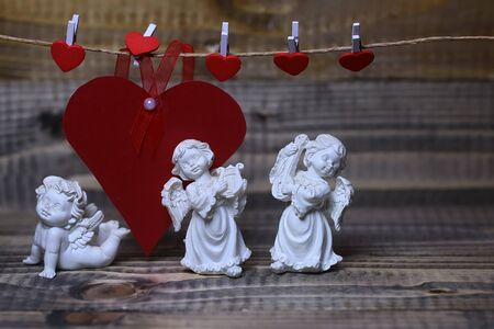 putto: Closeup view of three beautiful cupid angels decorative figurine near red paper greeting valentine card on hanging ribbon on clothes-peg with no people on wooden background, horizontal picture Stock Photo