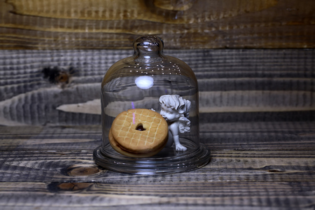 putto: Closeup view of beautiful cupid angel decorative figurine with round tasty biscuits under glassy flask indoor on dark brown wooden background, horizontal picture