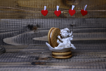 clothespeg: Closeup view of beautiful cupid angel decorative figurine near red paper greeting valentine clothes-peg in shape of heart with round pastry on wooden background, horizontal picture