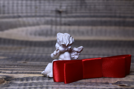 Closeup view of one beautiful cupid angel decorative figurine near red valentine silk ribbon bow with no people on wooden background copy space, horizontal picture