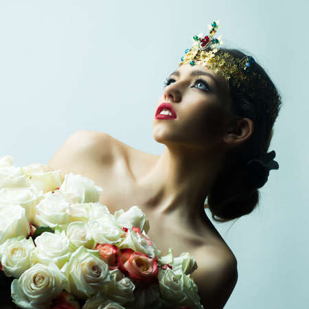 kingly: Portrait of one beautiful majestic royal queen with luxury precious shiny briht gold crown with colorful diamonds and gems holding big flower bouquet of many white and red roses, square picture