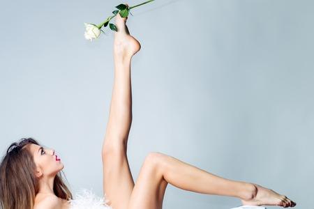 femme se deshabille: Longueur totale d'une belle jeune femme sexuelle nue avec droit corps mince déshabillée et les cheveux longs couché dans des pétales de fleurs jaunes sur blanc tenue de tissu rose en jambe levée en studio, horizontal