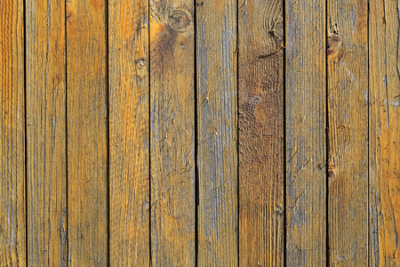 boarded: Photo closeup of old close boarded fence wooden palisade wood boards with knots loosing yellow paint on timber background, horizontal picture