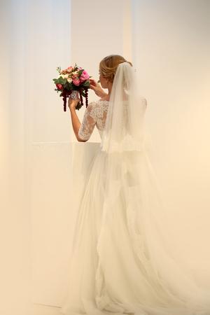 Foto van jonge bruid volledige lengte achteraanzicht het dragen van lange kant witte trouwjurk en bruids sluier die het mooie versierde boeket voor de ceremonie in handen op pastel achtergrond, verticale foto