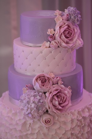 tiers: Photo closeup of traditional elegant delicious sweet four-layer wedding cake decorated with butter-cream roses on blurred violet background, vertical picture