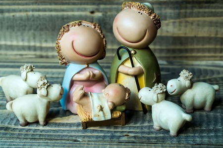 jesus standing: Closeup view of decorative celbrating Christmas and Jesus birth figurines of holy vergin Mary Josepd newborn child with few white sheeps standing on wooden background, horizontal picture