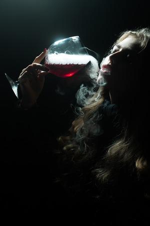 elixir: Primer retrato de vista de un solo hermosa sensual seria Mujer encantada enigm�tica joven que sostiene en la mano vaso lleno de l�quido con el humo del elixir m�gico de beuty y la vida y el secreto de la juventud