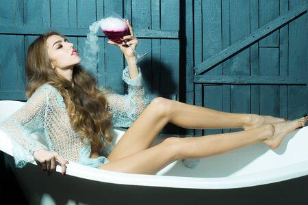elixir: Mujer sexual joven atractiva con el pelo rizado largo y recto cuerpo delgado en paño azul de punto sentado en la ficha de baño blanco sosteniendo vaso con líquido rojo con humo como elixir de belleza interior