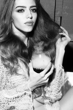 elixir: Cute young sexual woman with long curly hair and straight slim body in knitted cloth sitting in white bath tab holding drinking glass with liquid with smoke as elixir of beauty indoor black and white