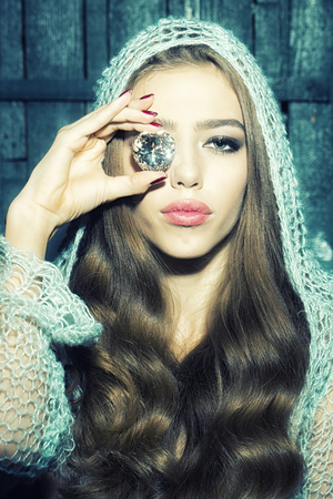 witchery: Portrait of one enchanted enigmatic beautiful sensual young woman with long lush curly hair in blue knitted cloth holding big magic white faceted stone precious gem as elixir of youth and beauty