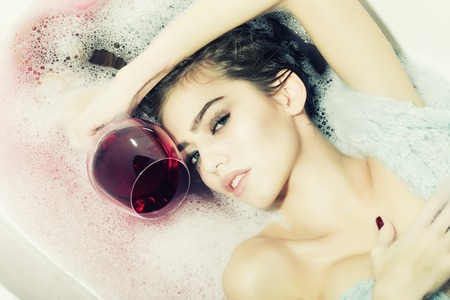 Closeup view portrait of attractive young girl with wet hair lying in white bath tab full of water and soap foam holding drinking glass with red liquid as elixir of beauty or desert wine indoor