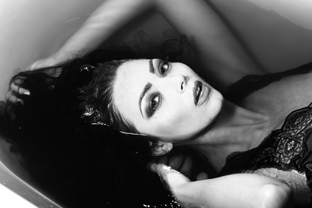 sensory: Closeup of one sexual young sensory attractive brunette woman with wet long curly hair and bright makeup lying in bath tab full of water taking shower in cloth black and white Stock Photo