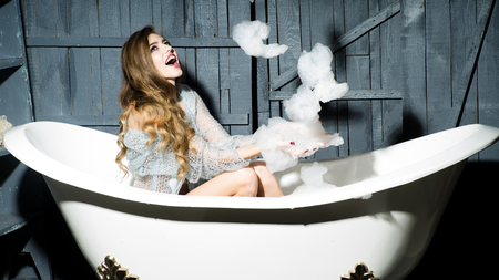 flirtatious: One beautiful sensual playful flirtatious young woman with long hair in blue knitted cloth sitting in white bath tub playing with soap foam indoor on wooden background