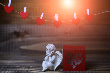 clothespeg: Closeup view of one beautiful cupid angel decorative figurine near red paper greeting valentine box near clothes-peg in shape of heart with no people on wooden background
