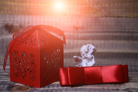 Closeup view of one beautiful cupid angel decorative figurine near red paper greeting valentine box in shape of heart near silk ribbon bow with no people on wooden background