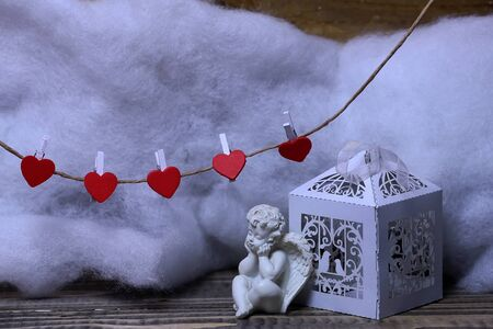 wadding: Closeup view of one beautiful cupid angel decorative figurine near paper greeting valentine box and hanging red clothes-peg in shape of heart with white wadding decorating snow