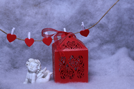 wadding: Closeup view of one beautiful cupid angel decorative figurine near red paper greeting valentine box and hanging clothes-peg in shape of heart with white wadding decorating snow Stock Photo