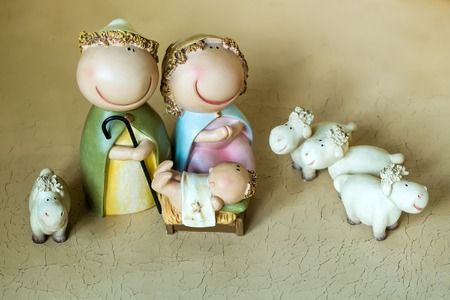 jesus standing: Closeup view of decorative celebrating Christmas and Jesus birth figurines of holy virgin Mary Joseph newborn child with few white sheep standing on light leather background Stock Photo