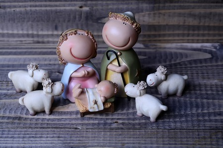 joseph: Closeup view of decorative celebrating Christmas and Jesus birth figurines of holy virgin Mary Joseph newborn child with few white sheep standing on wooden background Stock Photo