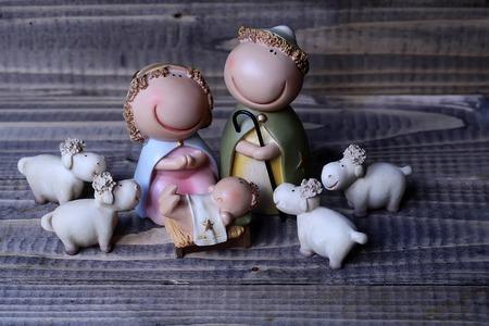 jesus mary joseph: Closeup view of decorative celebrating Christmas and Jesus birth figurines of holy virgin Mary Joseph newborn child with few white sheep standing on wooden background Stock Photo