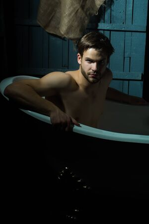 taking shower: One handsome serious sensual muscular young man with beautiful bare body sitting in white bath tub with foam taking shower looking forward indoor on wooden wall backdrop Stock Photo