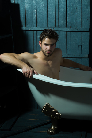 Één knappe seus sensuele gespierde jonge man met een mooie naakte lichaam zitten in witte badkuip met schuim nemen van een douche op zoek naar indoor op houten wand achtergrond