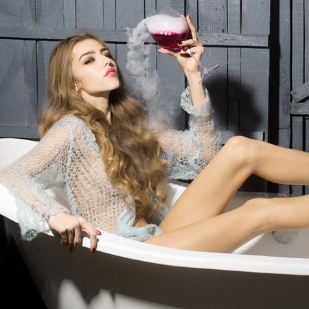 elixir: Mujer sexual joven atractiva con el pelo rizado largo y recto cuerpo delgado en pa�o azul de punto sentado en la ficha de ba�o blanco sosteniendo vaso con l�quido rojo con humo como elixir de belleza interior