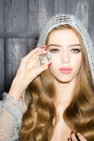 elixir: Retrato de un solo encantado enigm�tica mujer hermosa joven sensual con el pelo largo y rizado exuberante en pa�o azul de punto mantiene gran piedra blanca facetas gema preciosa magia como elixir de la juventud y la belleza Foto de archivo