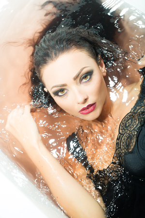 sensory: Closeup portrait of one sexual young sensory passionate attractive brunette woman with wet long curly hair and bright makeup lying in bath tab full of water taking shower in cloth, vertical picture Stock Photo