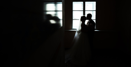window opening: Photo full length of dark silhouette of bridal couple bride and groom kissing in window opening blazed into glossy surface on wedding day black and white on indoor background, horizontal picture Stock Photo
