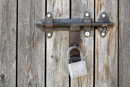 palisade: Photo closeup of padlock on old unpainted close boarded gate and fence wooden palisade wood boards with knots on timber background, horizontal picture Stock Photo