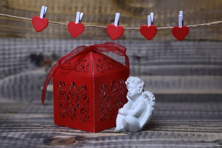 putto: Closeup view of one beautiful cupid angel decorative figurine near red paper greeting valentine box near clothes-peg in shape of heart with no people on wooden background, horizontal picture