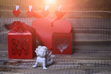 clothespeg: Closeup of one beautiful cupid angel decorative figurine near red paper greeting valentine box near clothes-peg in shape of heart with no people on wooden background copy space, horizontal picture