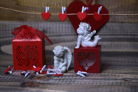Closeup view of few beautiful cupid angels decorative figurine near red paper greeting valentine box and card on hanging ribbon on clothes-peg with no people on wooden background, horizontal picture