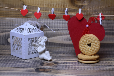 clothespeg: Closeup of beautiful cupid angel decorative figurine near white paper greeting valentine box and red card on hanging ribbon on clothes-peg with round cookie on wooden background, horizontal picture Stock Photo