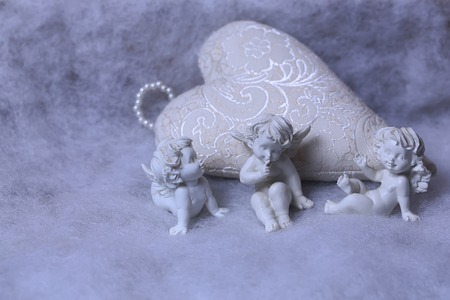 wadding: Closeup of beautiful soulful figurine composition of cupid angels for valentine day or christmas with small pillow in shape of heart lying on white wadding decorating snow, horizontal picture