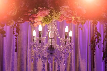 cutglass: Photo closeup of one classic cut-glass crystal chandelier lighting fixture with electric opal bulbs illuminating and arch decorated with fresh flowers on violet curtains background, horizontal picture