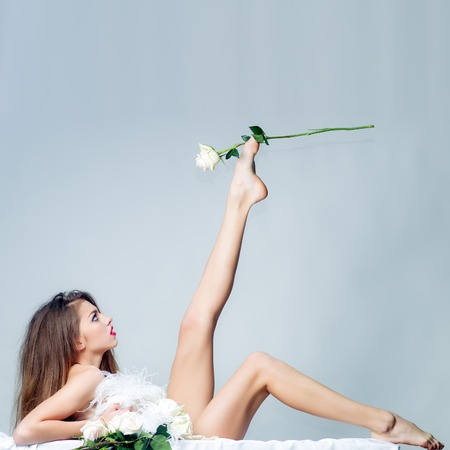naked legs: Full length of one beautiful naked sexual young woman with straight slim undressed body and long hair lying in yellow flower petals on white fabric holding rose in raised leg in studio, square photo