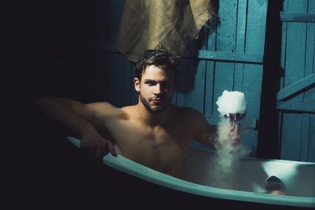 salud sexual: hombre sensual Un apuesto joven muscular seus con hermoso cuerpo desnudo sentado en la tina de baño blanca con el vidrio de retención de espuma con Luquid y el humo de interior en telón de fondo de pared de madera, cuadro horizontal