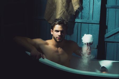 bathing man: One handsome serious sensual sexy muscular young man with beautiful bare body sitting in white bath tub with foam holding glass with luquid and smoke indoor on wooden wall backdrop, horizontal picture Stock Photo