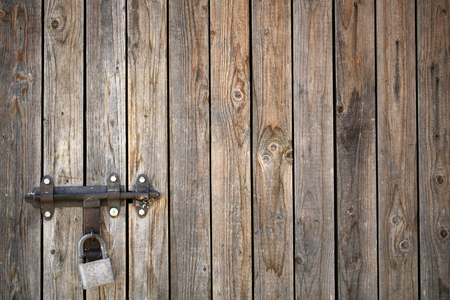 boarded: Photo of old unpainted close boarded gate and fence wooden palisade wood boards with knots padlock on timber background, horizontal picture