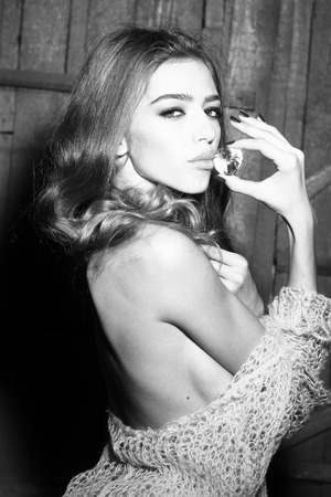 elixir: Uno encantado enigmática mujer hermosa joven sensual con el pelo largo y rizado exuberante en tela de punto mantiene gran magia blanca piedra facetas gema preciosa como elixir de la juventud y la belleza en blanco y negro