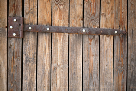 unpainted: Photo closeup of rusty butt on old unpainted rough gate and close boarded fence wooden palisade wood boards with knots on timber background, horizontal picture
